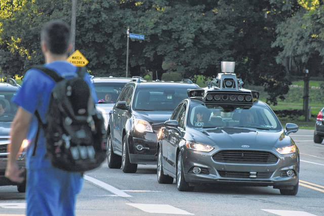 An Uber self-driving Ford Fusion sits at a traffic light on Beechwood Boulevard and waits to turn onto Fifth Avenue in Pittsburgh.