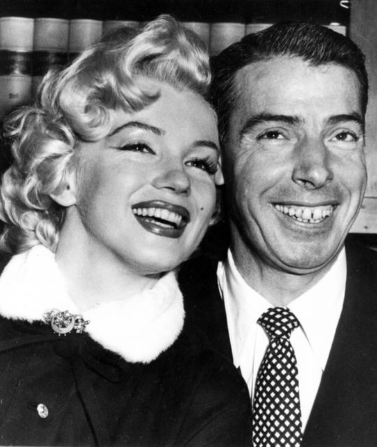 FILE - In this Jan. 14, 1954 file photo, New York Yankees' Joe DiMaggio, right, poses with actress Marilyn Monroe, as they wait for their marriage ceremony in San Francisco. The black dress that a distraught Marilyn Monroe wore to a 1954 press conference announcing her separation from baseball legend Joe DiMaggio is going up for auction. KruseGWS Auctions announced Wednesday that the simple wool dress with a zippered turtleneck front will be up for bidding starting on March 30. Monroe was wearing it in Beverly Hills on Oct. 6, 1954 when she stepped out amid a mob of cameras and reporters to announce the split in a marriage. (AP Photo, File)
