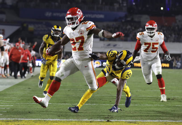 "FILE - In this Nov. 19, 2018, file photo, Kansas City Chiefs running back Kareem Hunt (27) scores a touchdown ahead of Los Angeles Rams free safety Lamarcus Joyner (20) as Chiefs offensive guard Cameron Erving (75) looks on during the first half of an NFL football game, in Los Angeles. The Cleveland Browns have signed Kareem Hunt, the running back cut by Kansas City in November after a video showed him pushing and kicking a woman the previous February.  Cleveland general manager John Dorsey, who drafted Hunt while working for Kansas City, on Monday, Feb. 11, 2019,  said the Browns ""fully understand and respect the complexity of questions and issues in signing a player with Kareem's history and do not condone his actions."" (AP Photo/Marcio Jose Sanchez, File)"