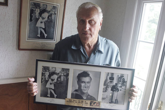 In this July 2, 2009, photo George Mendonsa poses for a photo in Middletown, R.I., holding a copy of the famous Alfred Eisenstadt photo of Mendonsa kissing a woman in a nurse's uniform in Times Square on Aug. 14, 1945, while celebrating the end of World War II, left. Mendonsa died Sunday. He was 95. It was years after the photo was taken that Mendonsa and Greta Zimmer Friedman, a dental assistant in a nurse's uniform, were confirmed to be the couple.