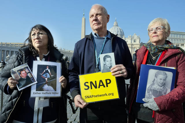 Survivors Network of those Abused by Priests (SNAP) President Tim Lennon from Tucson, Ariz., center, and SNAP members Esther Hatfield Miller from Los Angeles, Calif., left, and Carol Midboe from Austin, pose for pictures during interviews with the media in St. Peter's Square at the Vatican during Pope Francis' general audience, Wednesday, Feb. 20, 2019. Organizers of Pope Francis' summit on preventing clergy sex abuse met with a dozen survivor-activists who have come to Rome to protest the Catholic Church's response to date and demand an end to decades of cover-up by church leaders. (AP Photo/Luigi Navarra)