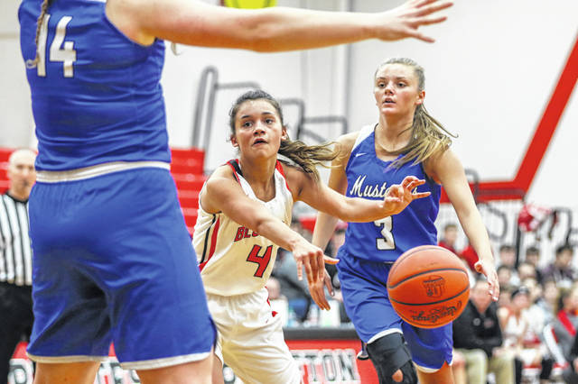 Kayla White of Bluffton dishes the pass after driving against the defense of Allen East's Ally Richardson (3) and Lauren Criblez on Monday night during the Northwest Conference matchup at Bluffton.