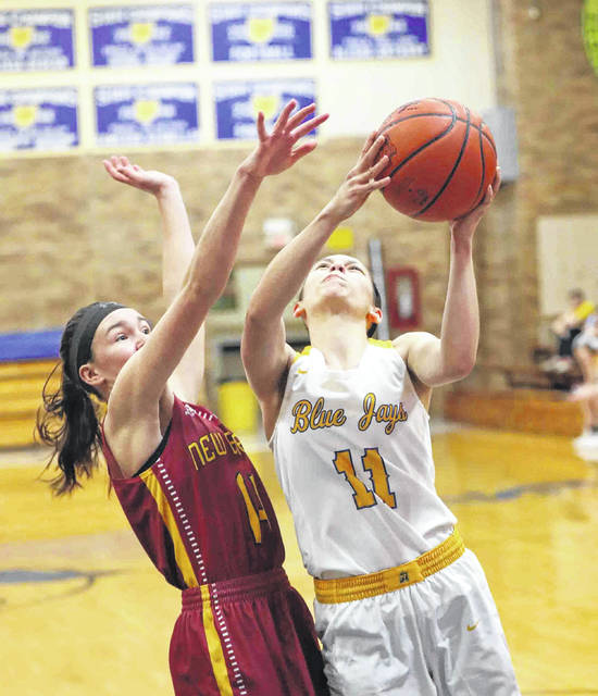 Paige Gaynier of Delphos St. John's put sup a shot against New Bremen's Abbi Thieman during Thursday night's Midwest Athletic Conference game at Robert A. Arnzen Gymnasium in Delphos.