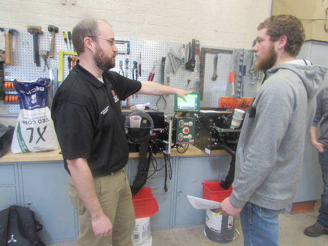 Dewey Mann, Ohio State lecturer for agricultural systems management, speaks to Zach Moehrman, Patrick Henry High School senior, about a stand that tests the accuracy of the meter on each row unit of a planter.