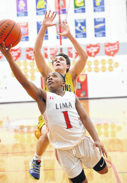 Lima Senior's Khalil Luster puts up a shot against Ottawa-Glandorf's Owen Hiegel during Tuesday night's game at Lima Senior.