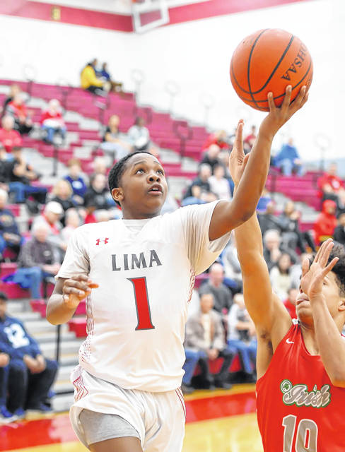Lima Senior's Khalil Luster puts up a shot against Toledo Central Catholic's Cameron Awls during Tuesday night's Three Rivers Athletic Conference game at Lima Senior High School.