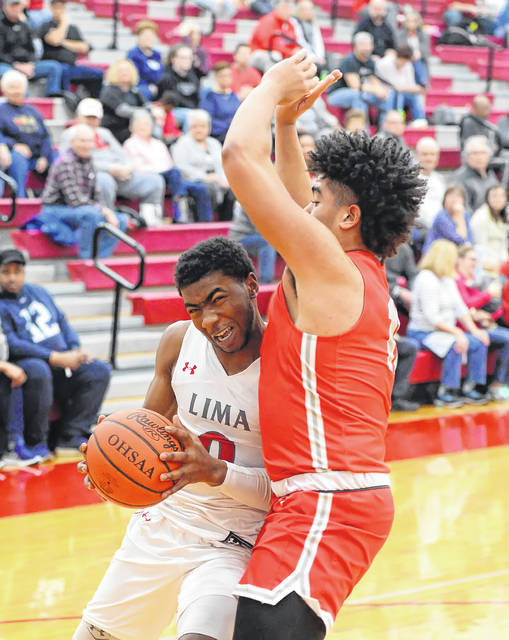 Lima Senior's Da'San Clair drives against Toledo Central Catholic's Kendal Marshall during Tuesday night's Three Rivers Athletic Conference game at Lima Senior High School.