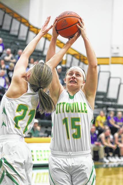 Ottoville's Haley Hoersten (15) and Nicole Knippen go up for a rebound during Saturday night's Putnam County League game against Leipsic at Ottoville.