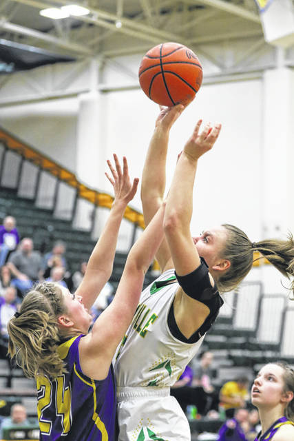 Ottoville's Brynlee Hanneman goes for a shot against Leipsic's Liz Scheckelhoff during Saturday night's Putnam County League game against Leipsic at Ottoville.