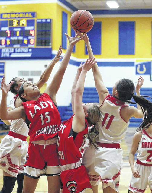 Perry's Makiah Denson (15) and Lily Floyd battle for a rebound with New Knoxville's Jaclyn Leffel (11) and Tasia Lauth during a Wednesday night Division IV girls sectional game at St. Marys.