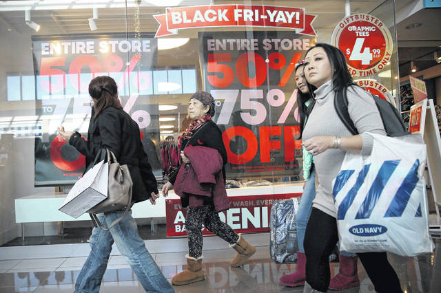 Shoppers walk past a Black Friday advertisement at Cherry Hill Mall in Cherry Hill, N.J., on Friday, Nov. 23, 2018.