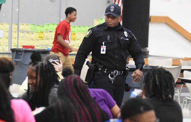 Lima Police School Resource Officer, D'Ante Barginere walks pass Lima West Middle School students during lunch on Tuesday afternoon.