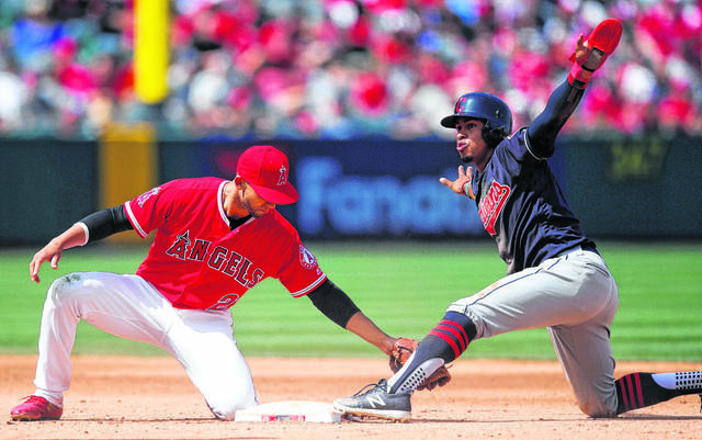 Francisco Lindor, of the Cleveland Indians, right, gestures after stealing second base against Los Angeles Angels' Andrelton Simmons during a game last season. The Indians are favored to win the American League Central Division again this season.