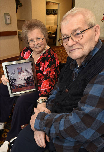 Marie Spangler holds her wedding photo with her husband Roger at Meadows of Kalida on Tuesday.