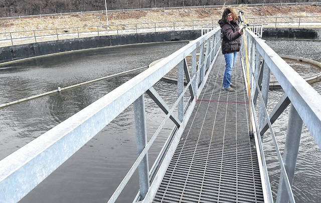 """Jessica Preston, a wastewater operator for the City of Lima, performs a """"slug test"""" at the city's wastewater treatment plant. Area governments face increasing competition to fill jobs, leading some to work with area schools and colleges to create internship possibilities."""