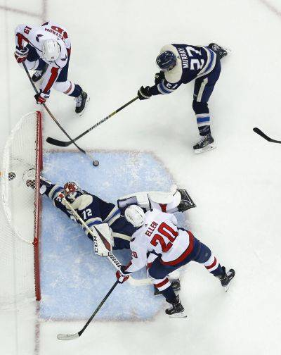 The Blue Jackets' Sergei Bobrovsky (72) makes a save as teammate Ryan Murray, top right, tries to clear the puck away from Washington's Nicklas Backstrom, top left,  and Lars Eller Tuesday night's game in Columbus. The Blue Jackets beat the Capitals 3-0. (AP photo)
