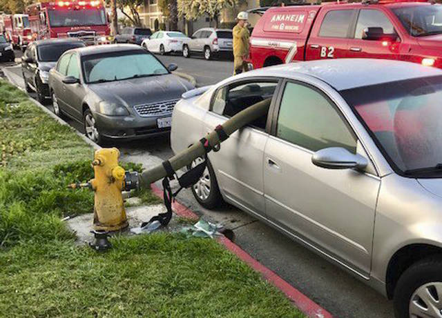 "This Feb. 26, 2019 photo provided by the Anaheim Fire Department and Anaheim Police Department shows a car with a firehose running through the rear side windows in Anaheim, Calif. A California fire department enflamed some social media users but delighted others by posting pictures of the busted-out windows of a car that parked in front of a fire hydrant. In a Twitter thread posted Wednesday, the Anaheim Fire Department asked the public: ""Ever wonder what happens when a car is parked in front of a fire hydrant and a fire breaks out."" (Anaheim Fire Department and Anaheim Police Department via AP)"