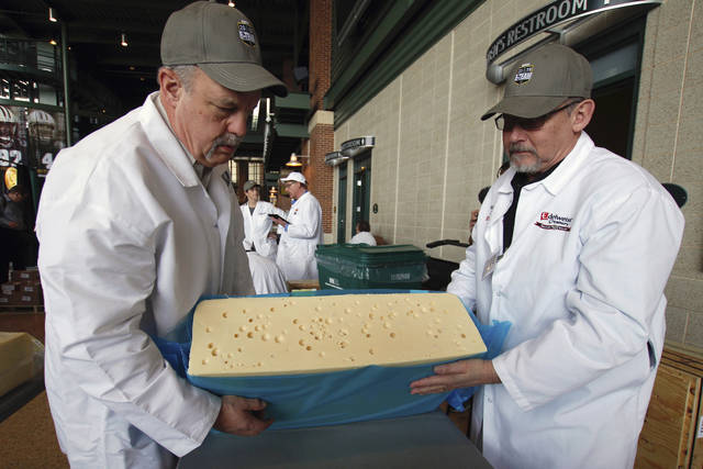 Steve Stettler, left, and Bruce Workman cut a piece a swiss cheesevat the United States Championship Cheese Contest  Tuesday, March 5, 2019 in Green Bay, Wis. The three-day event includes more cheese, butter and yogurt makers than ever before. It's is considered the largest technical cheese, butter and yogurt competition in the country. (AP Photo/Carrie Antlfinger)