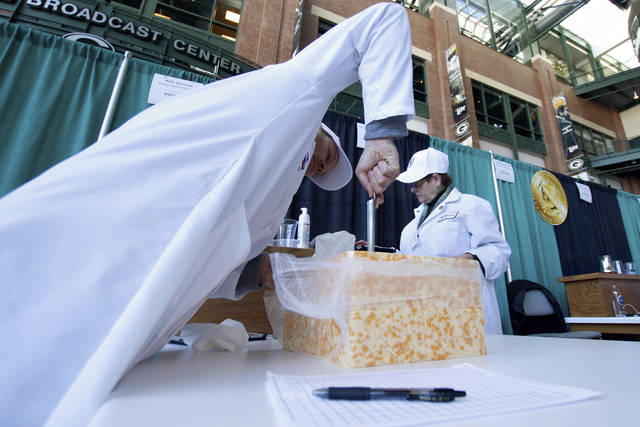 Judge Ben Novak attempts to obtain a piece of marbled curd cheese Tuesday, March 5, 2019 at the United States Championship Cheese Contest in Green Bay, Wis. The three-day event includes more cheese, butter and yogurt makers than ever before. It's is considered the largest technical cheese, butter and yogurt competition in the country. (AP Photo/Carrie Antlfinger)