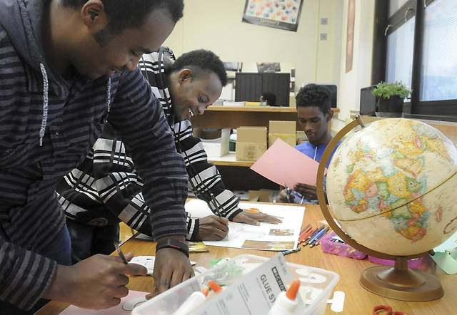 FILE - In this Dec. 21, 2015 file photo, Mohamed Obeyd, left, and Abukar Adnan design posters for a fundraiser at an Adult Basic Education English class in Mankato, Minn. On Friday, March 8, 2018, The Associated Press has found that stories circulating on the internet that President Barack Obama resettled 70,000 Somalian refugees in Minnesota, are untrue. According to data from the U.S. Department of State's Refugee Processing Center, the state received 6,320 Somalian refugees during his tenure. (Pat Christman/The Free Press via AP)
