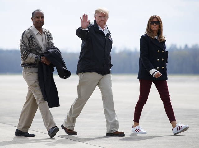 President Donald Trump, first lady Melania Trump and Secretary of Housing and Urban Development Ben Carson walk from Marine One to board Air Force One at Lawson Army Airfield, Fort Benning, Ga., Friday en route Palm Beach International Airport in West Palm Beach, Fla., after visiting Lee County, Ala., where tornados killed 23 people.