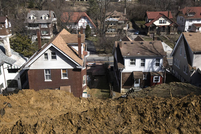 This Thursday, Feb. 21, 2019 photo shows the backyard of the house in the 700 block of Mitchell Avenue in North Avondale neighborhood of Cincinnati. In September 2018, a landslide occurred behind the house. The City of Cincinnati in a statement said Department of Buildings and Inspections has orders open to repair the current situation and prevent the situation from worsening. (Albert Cesare/The Cincinnati Enquirer via AP)