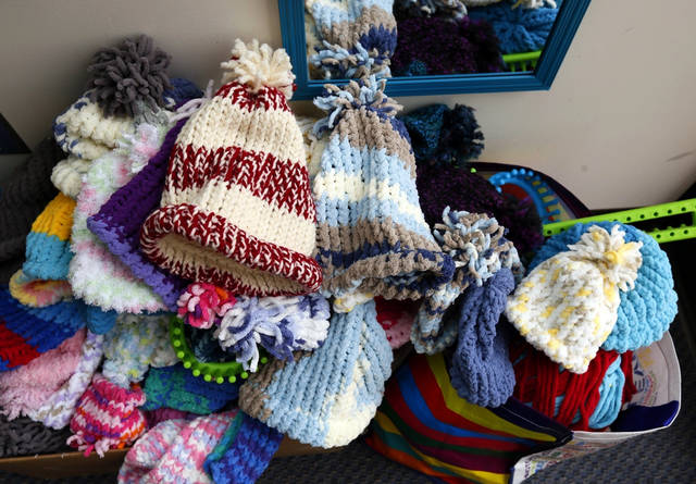 In this Feb. 11, 2019 photo, hats knit by Ohio Dominican students sit in a pile in Columbus, Ohio. The students meet regularly and knit hats with the plans on donating them to the homeless and others. (Eric Albrecht/The Columbus Dispatch via AP)