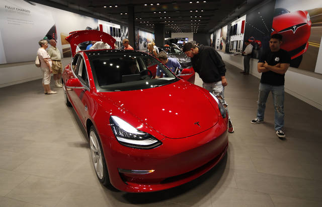 FILE- In this July 6, 2018, file photo prospective customers confer with sales associates as a Model 3 sits on display in a Tesla showroom in the Cherry Creek Mall in Denver. Tesla is walking back its plan to close most retail stores worldwide in a move the company says will force it to raise prices on most of its electric vehicles. The company still will move to online-only sales, but now says it won't close as many stores as originally thought. Tesla announced last month that it would shutter most of its stores to cut costs so it could sell its lower-priced Model 3 for $35,000. (AP Photo/David Zalubowski, File)