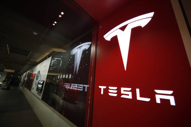 FILE- In this Feb. 9, 2019, file photo, a sign bearing the company logo is displayed outside a Tesla store in Cherry Creek Mall in Denver. Tesla is walking back its plan to close most retail stores worldwide. The company says it still plans to move to fully online sales but it won't close as many stores as originally thought. Tesla announced last month that it would shutter most of its stores to cut costs so it could make money on the $35,000 Model 3 electric car. Tesla now says it closed 10 percent of its stores, but a few of those will be reopened.   (AP Photo/David Zalubowski, File)