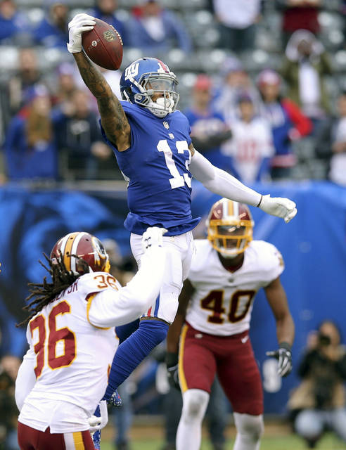 FILE - In this Oct. 28, 2018, file photo, New York Giants wide receiver Odell Beckham Jr. (13) makes a one handed catch against Washington Redskins safety D.J. Swearinger (36) and linebacker Josh Harvey-Clemons (40) during an NFL football game, in East Rutherford, N.J. No longer a punching bag, the Browns are punching back. From hopeless to hopeful. Finally.  In landing Beckham, one of the game's most electrifying players, the Browns have risen from the deepest depths imaginable in just a year. (AP Photo/Brad Penner, File)