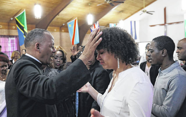 "Pastor Melvin Trent, left, prays with a parishioner during a service at the New Beginnings Outreach Ministries, Sunday, March 3, 2019, in Youngstown, Ohio. Trent stood before about 150 members of his church in early February and told them he was leaving. His wife, an engineer with GM, was being sent to its SUV plant in Arlington, Texas. Trent, 55, who retired after 35 years with the automaker, said it was a ""no-brainer"" to accept the relocation but not an easy decision."