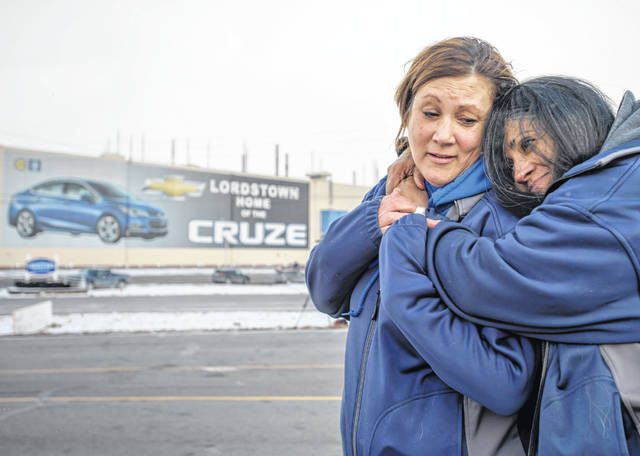 Tammy Daggy, of Salem, Ohio, and Marisol Bowers, of Youngstown, Ohio, both employees of General Motors for 24 years, hug as people gather in front of the General Motors assembly plant, Wednesday, March 6, 2019, in Lordstown, Ohio. Wednesday is the last day of the plant's Chevrolet Cruze production, a move that will eliminate nearly 1,700 hourly jobs and idle the plant. (Steph Chambers/Pittsburgh Post-Gazette via AP)