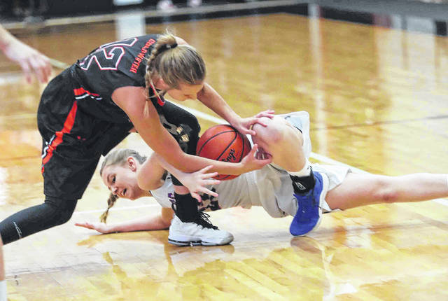 Coldwater's Courtney May, left, and Liberty-Benton's Schy Shepherd battle for a loose ball during a Thursday night Division III district semfinal at the Elida Fieldhouse.