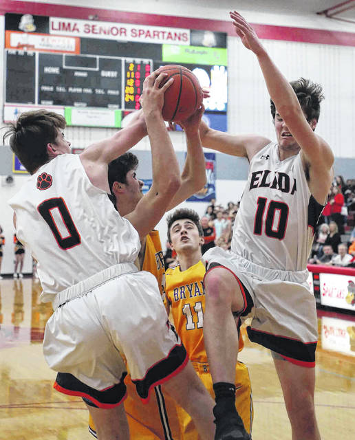 Elida's Matt Fish, left, and Max Parker battle for a rebound against Bryan's Titus Rohrer during a Friday night Division II sectional final at Lima Senior.