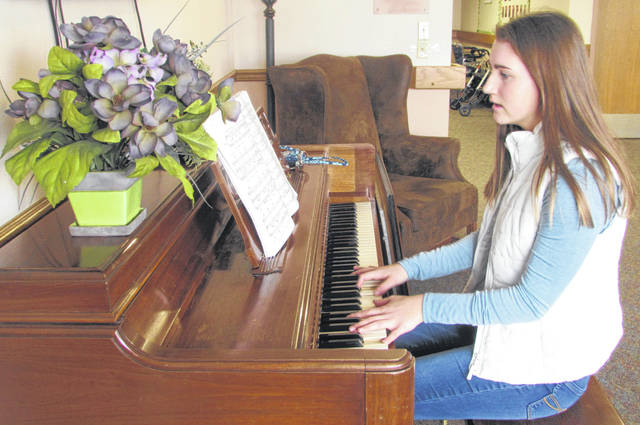 "Delphos Jefferson High School Sophomore Emily Dienstberger plays Elvis Presley's ""I Can't Help Falling In Love With You"" for residents at Sarah Jane Nursing Home."