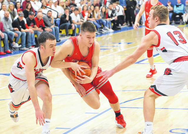 Columbus Grove's Evan Hopkins drives between Arlington's Ty Webb, left, and Ivan Berry during Friday night's Division IV district championship game at Findlay High School.