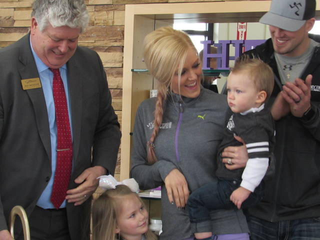 New Anytime Fitness owner Alexa Miller, center, celebrates the fitness club's refresh with her husband Brandon, right, son Cruz, daughter Cozy and Lima/Allen Chamber of Commerce President & CEO Jed Metzger.