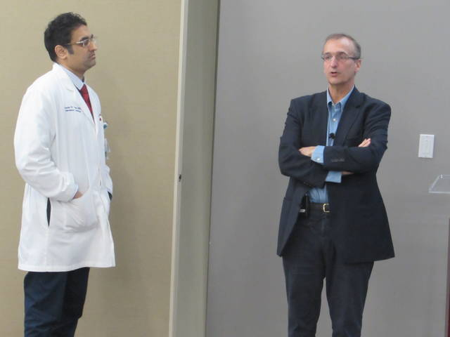 Dr. Jean-Claude Laborde, right, talked with Dr. Sandeep Patel, left, and other physicians at Mercy Health - St. Rita's Medical Center on Tuesday about his role in developing the transcatheter aortic valve replacement procedure.