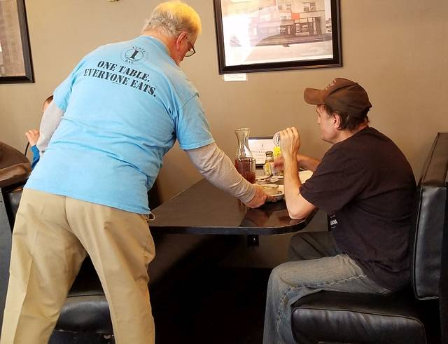 David Trinko | The Lima News Philip Compton, a co-founder of Table One in Kenton, delivers a bowl of soup to Brian Sprouse, of Kenton, on Tuesday morning. The restaurant lets patrons pay what they can for a meal or volunteer to work instead.
