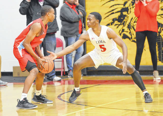 Lima Senior's Jadakis Mack defends Bowsher's Sherod Brooks during a Friday night Division I sectional final at Fostoria High School.