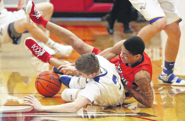 Perry's Chazz Jackson, right, and Marion Local's Alex Eyink battle for control of a loose ball during a Tuesday night Division IV district semifinal at Wapakoenta.
