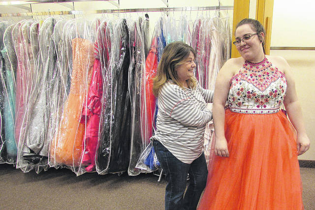 "Kathy Hilty, a mentor with Big Brothers Big Sisters of Hardin County, helps her ""little,"" Baylee Aldrich, try on a prom dress at the Findlay Mall recently."