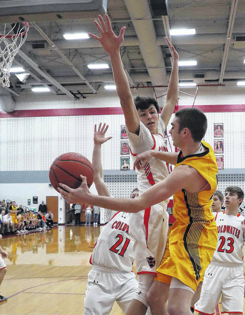 Ottawa-Glandorf's Braden Fortman makes a pass against Coldwater's Justin Schwieterman (21) and Cole Frilling during Saturday's Division III district final at Lima Senior.