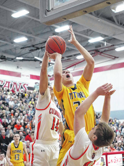 Coldwater's Cole Frilling (14) defends a shot by Ottawa-Glandorf's Ben Westrick as Noah Miller also defends for Coldwater during Saturday's Division III district final at Lima Senior.