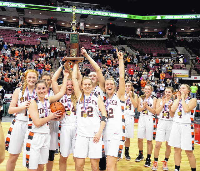Minster players hoist the Division IV state championship trophy Saturday at Value City Arena in Columbus.