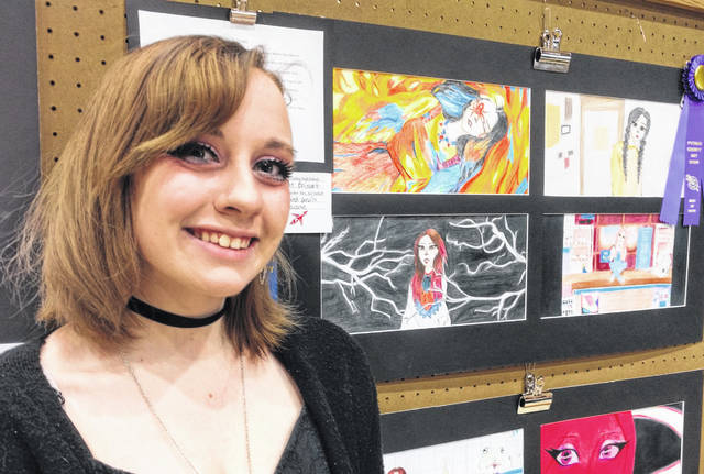 """Katherine Boisvert from Pandora-Gilboa High School, poses next to her colored pencil drawing, """"Loonaverse"""". She was one of 15 students who won a """"Best of Show"""" ribbon in the Putnam County Art Show Sunday at Kalida High School."""