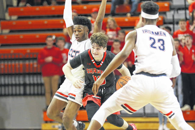 Shawnee's John Barker of Shawnee powers through the defense of Cleveland Central Catholic's Deshaun Nettles (23) and Jayden Williams during a Thursday night Division II regional semfinal at Bowling Green State University's Stroh Center.