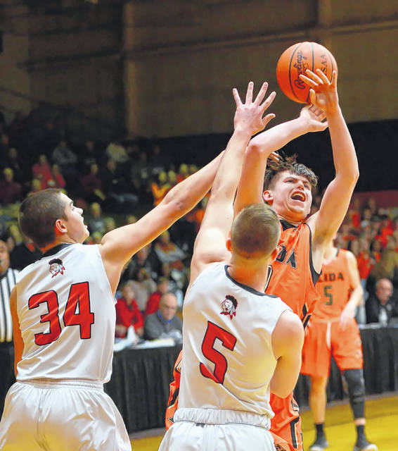Elida's Matt Fish shoots against Shawnee's Tyson Elwer, left, and Johnny Caprella during Wednesday's Division II District game at the ONU Sports Center in Ada.