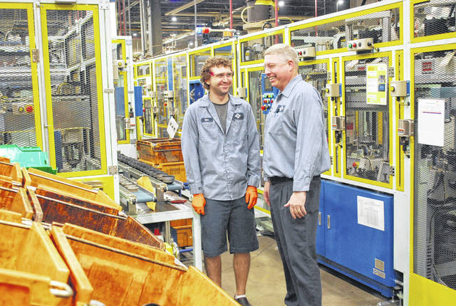 Tyler Wilson, left, a six-year employee of SumiRiko Ohio Inc., talks with Executive Vice President Steve Unterbrink on the production floor of the Bluffton firm. The company is a major supplier of rubber anti-vibration products for the automotive industry.