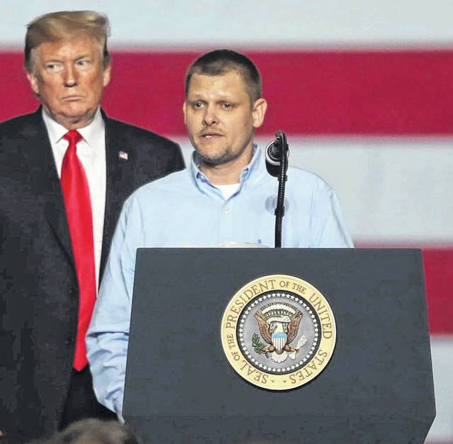President Donald Trump stands with Adam Stahler, a quality systems engineer, as he speaks to the crowd of employees and other selected officials after his tour of the Joint Systems Manufacturing Center on Wednesday evening.